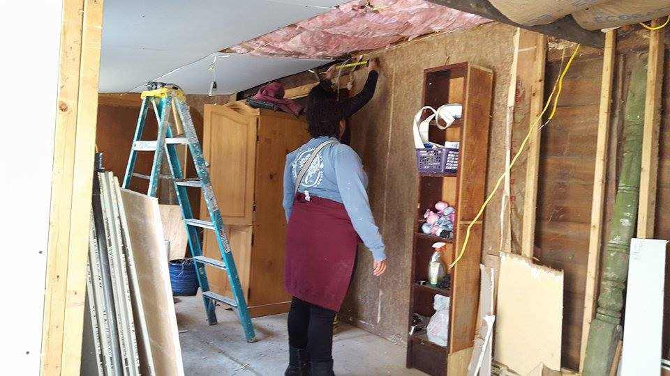 University of Richmond students installing sheetrock in Brandi Wright's old cabin at Berwind Lake. The cabin was built in 1856